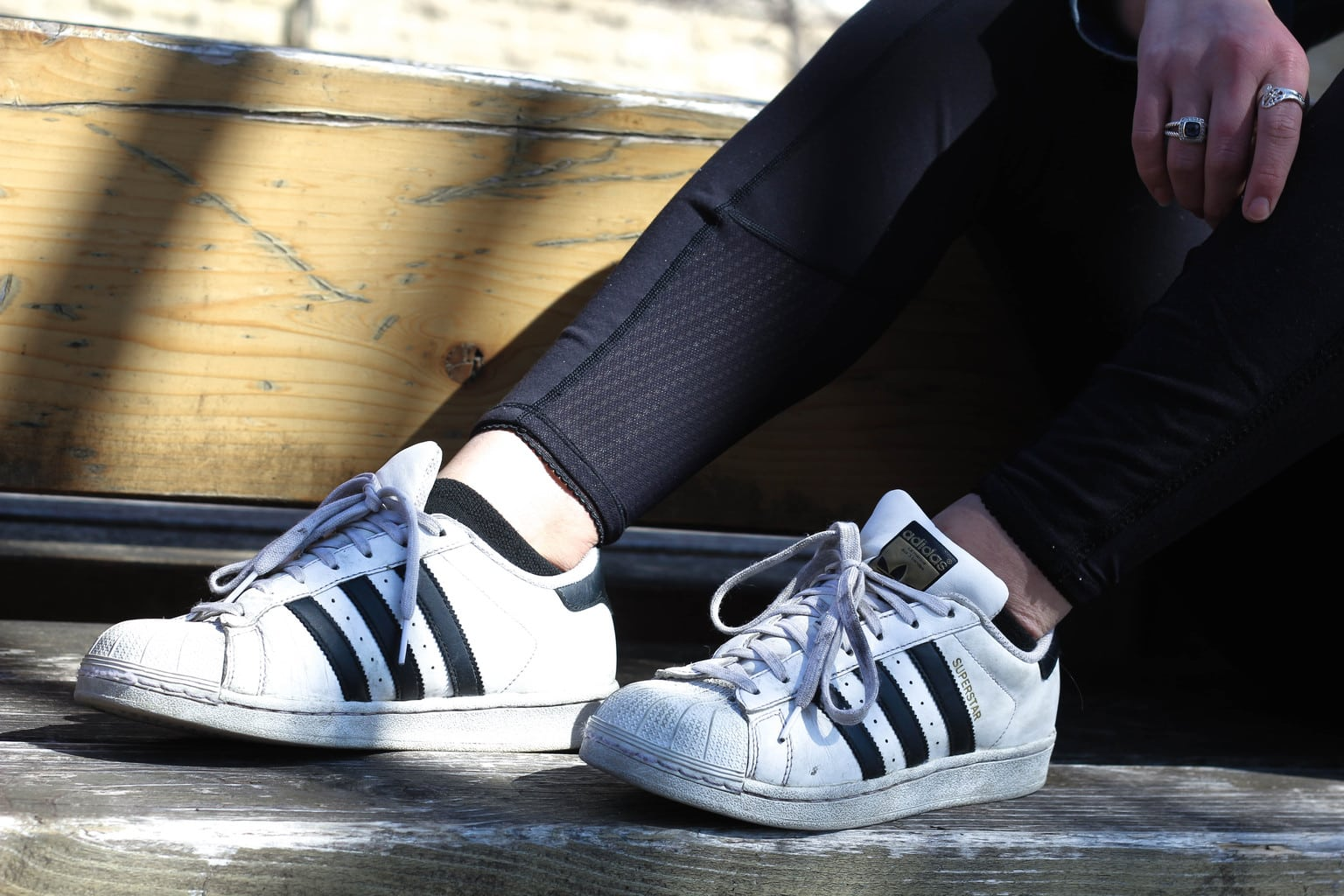 Bailey wears white and black worn-in Adidas all star sneakers with her athletic leggings.