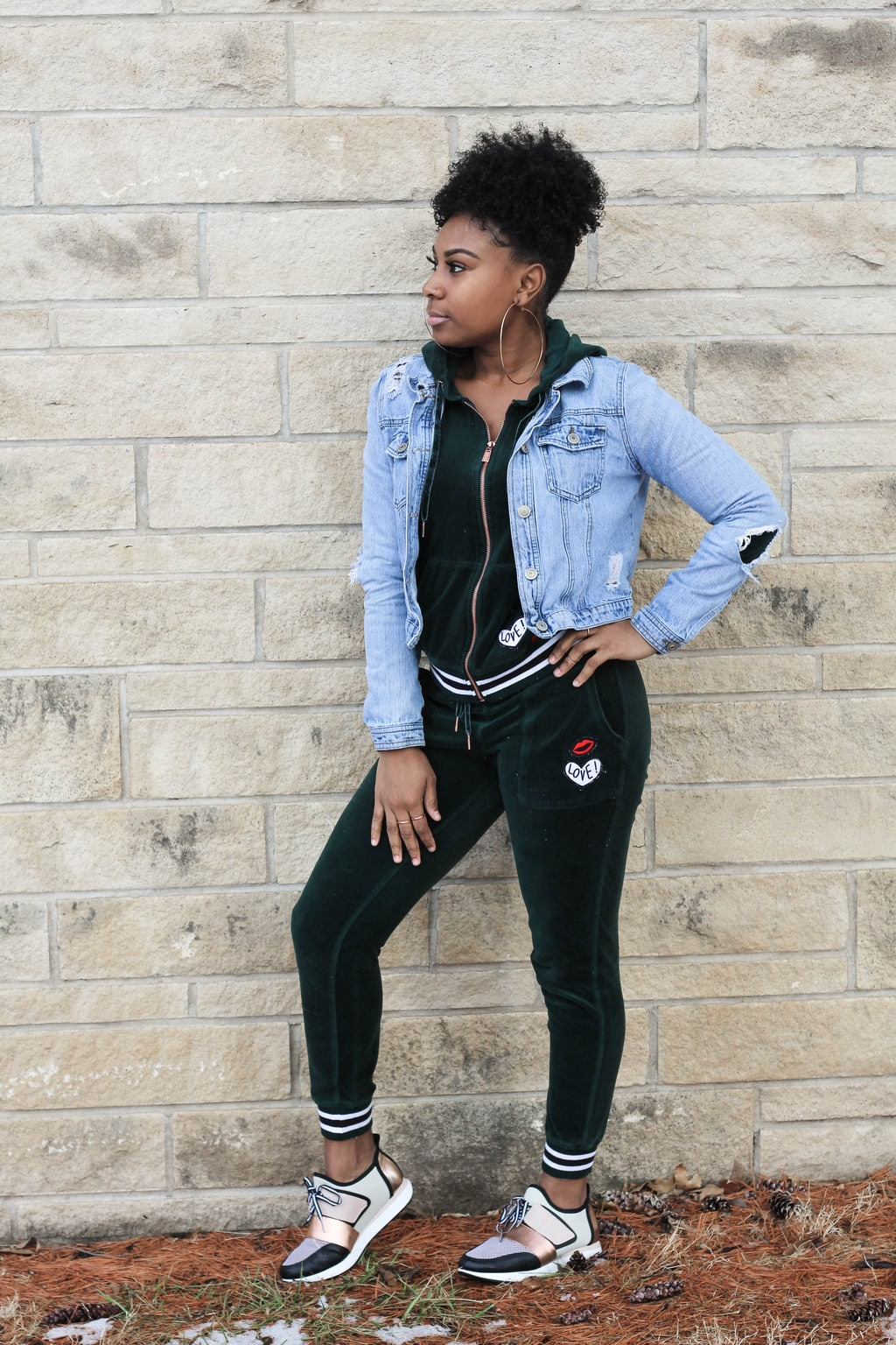 Kansas State University student Chaunice wears a green velour athletic sweatsuit with cropped jogger pants with embroidered lips and love patches and a matching hoodie with a rosegold zipper. She layered on a light-wash distressed denim jacket, giant gold hoop earrings, and crisp black, white, and rosegold sneakers.
