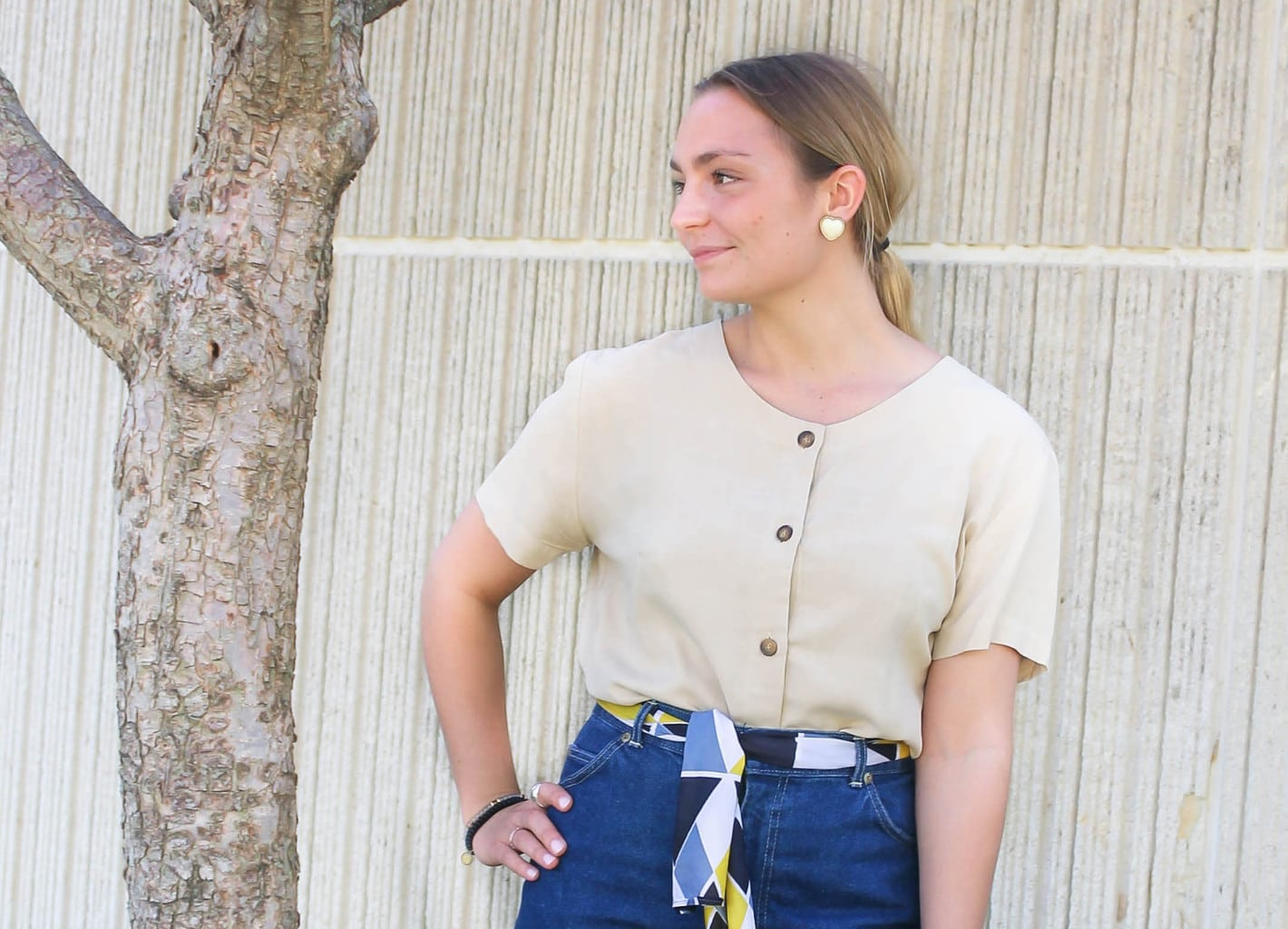 Emilee's pale yellow scoop neck top with brown buttons is tucked into her high-waisted jeans.