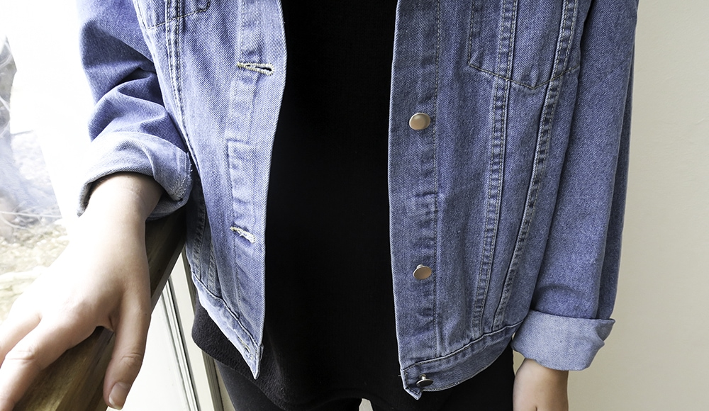 Hannah wears a black tee with a light-wash distressed denim oversized jacket with the sleeves rolled up.