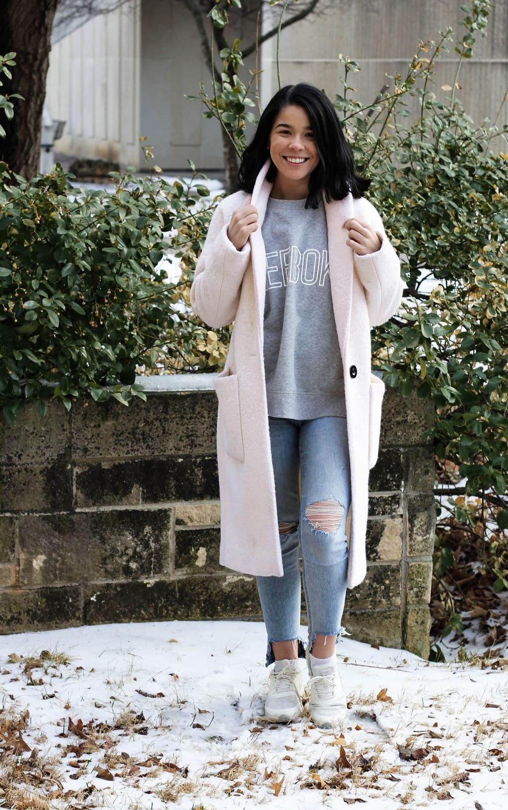 Kansas State University student Jessie sports a basic grey Reebok tee with distressed light-wash skinny jeans, white sneakers, and a long, baby pink coat.