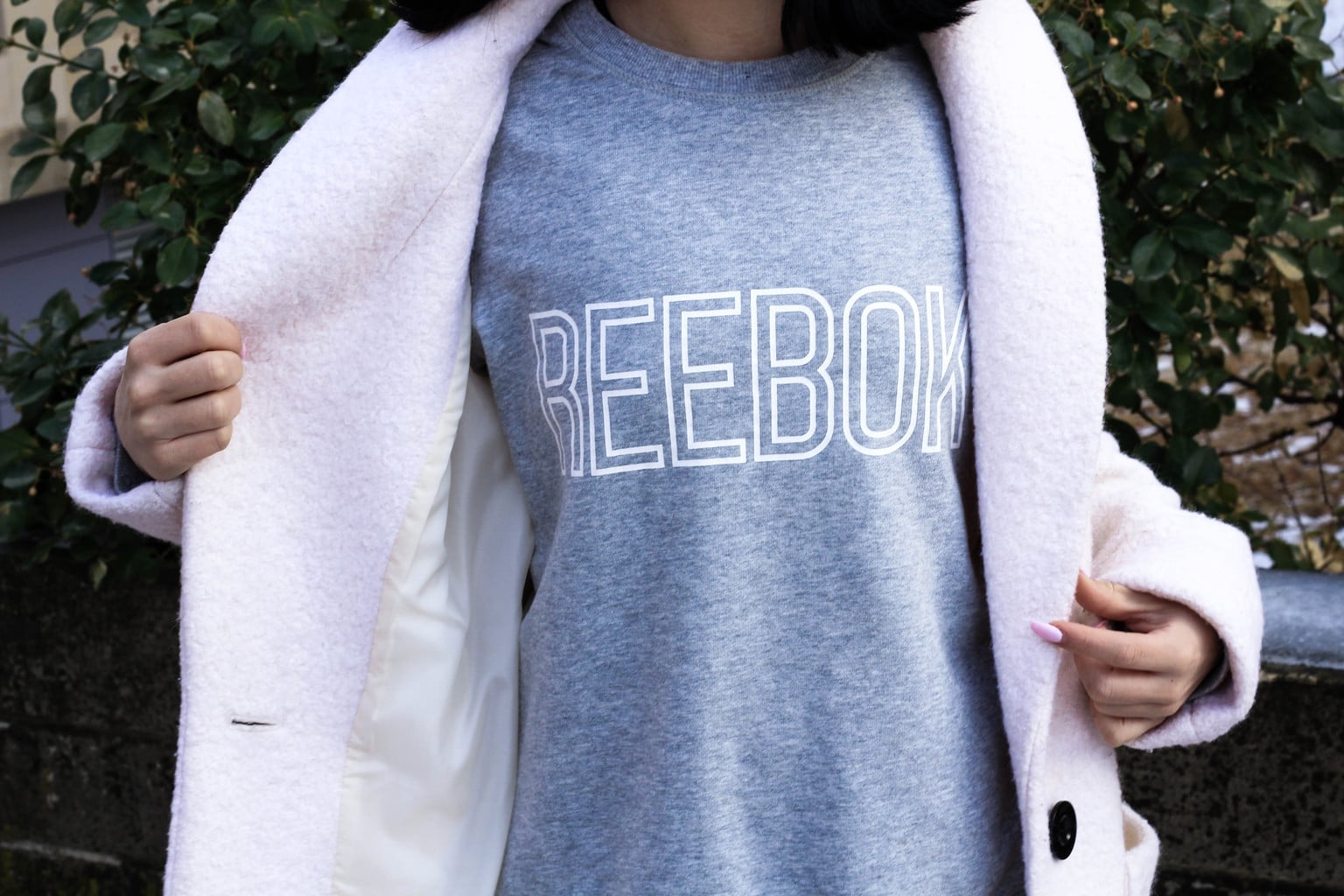 Jessie wears a loose-fitted  casual vintage style grey Reebok tee with her baby pink winter coat.