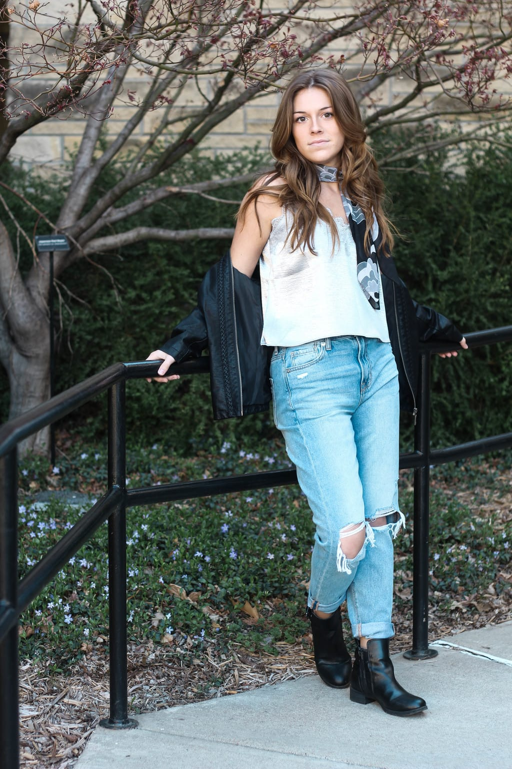 Maddie, a student at Kansas State University, wears a metallic silver slip camisole with lace trim, a pair of baggy distressed light-wash denim boyfriend jeans, flat black Chelsea booties, a leather jacket, and a grey and black scarf tied as an ascot.