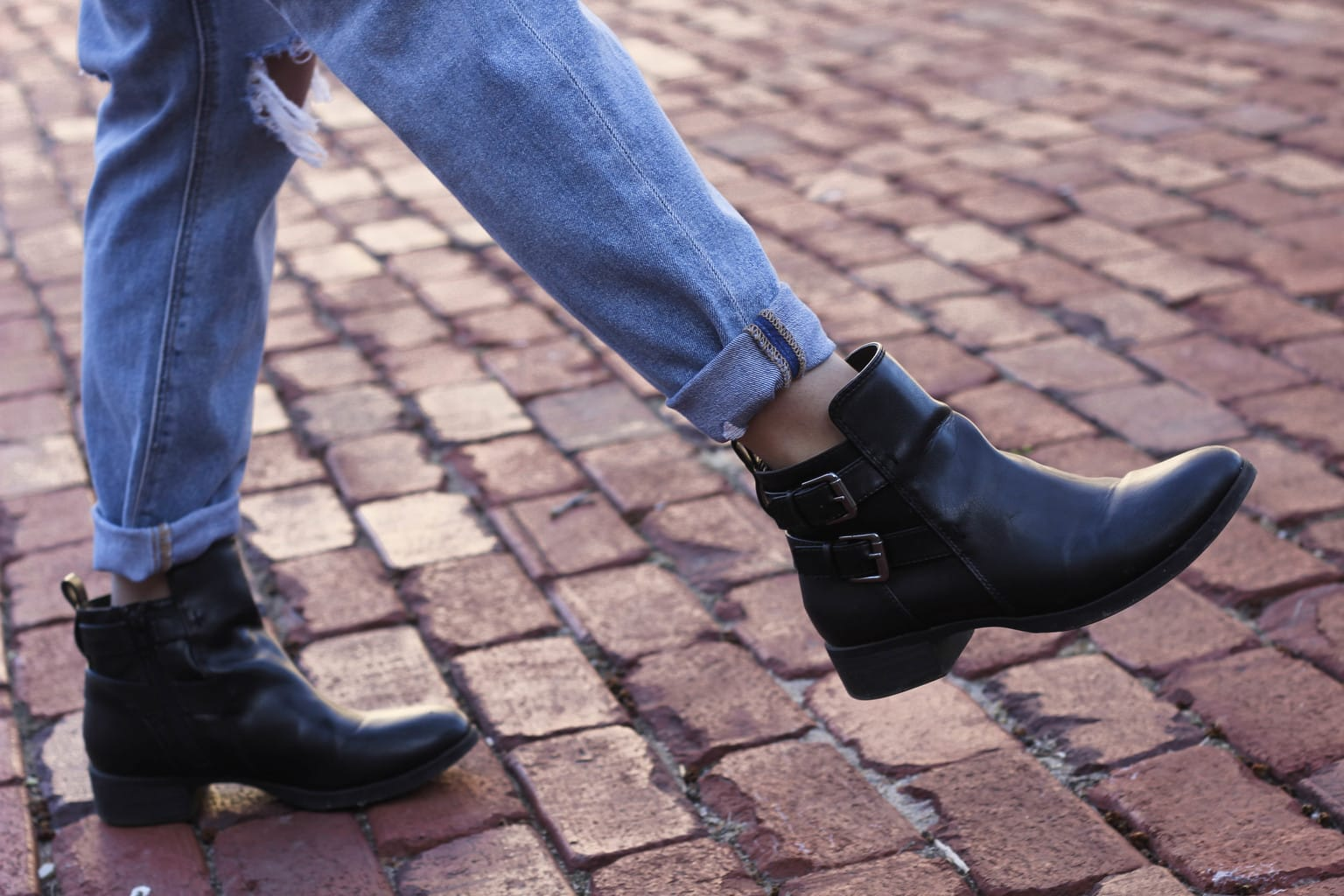 Maddie's black riding booties are flat with two silver buckles on the outside.