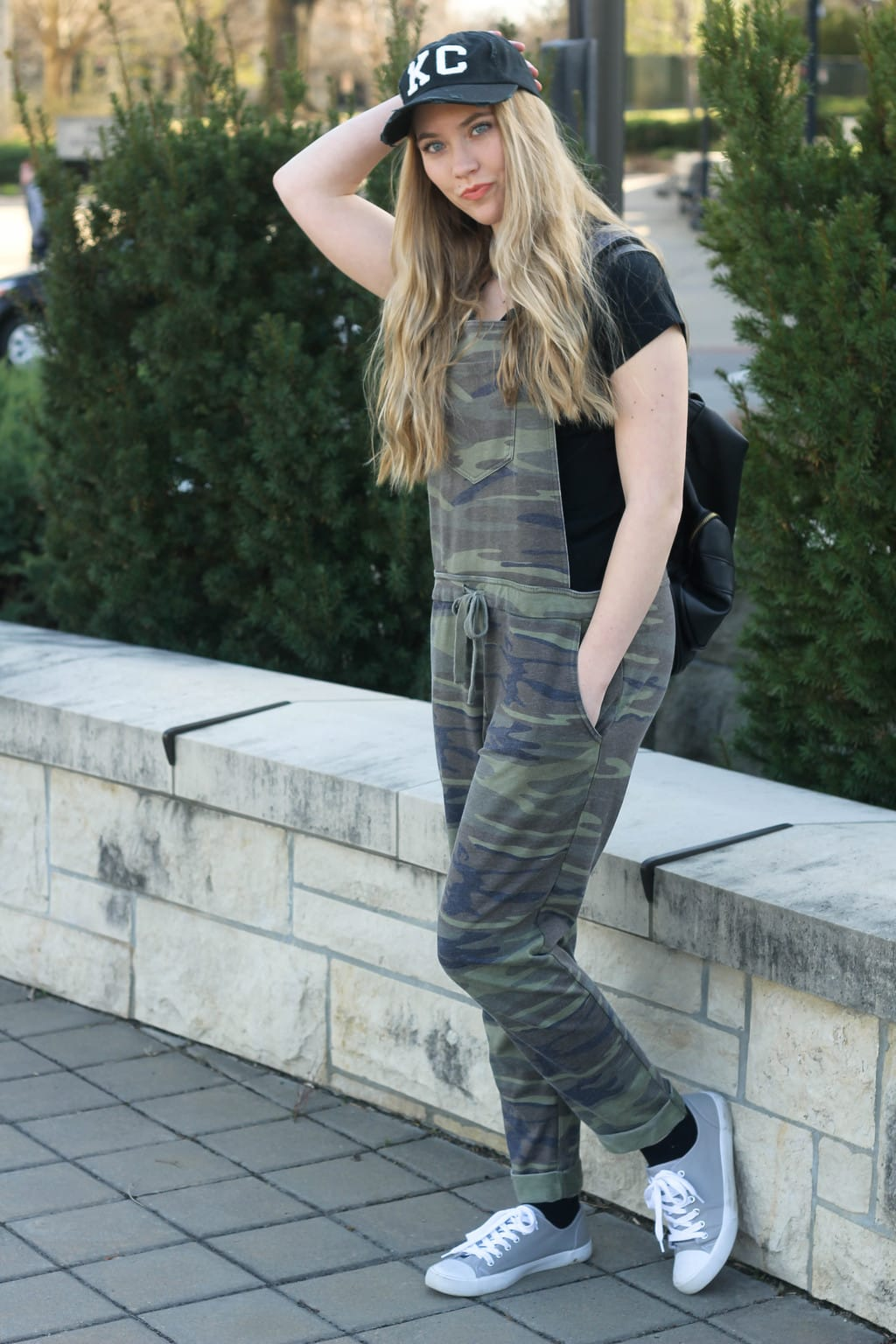 Monica, a student at Kansas State University, sports a relaxed knit camoflauge pair of overalls with a simple black tee, a black and white KC ballcap, a black backpack, and grey sneakers.