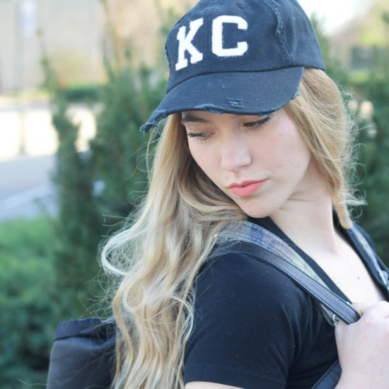 "Monica's tattered and worn black ballcap has ""KC"" patches on the front."