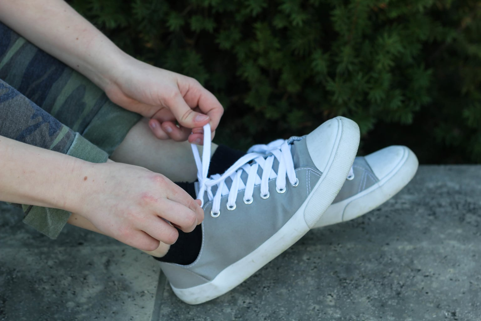 Monica wears her grey and white canvas sneakers with black ankle socks.