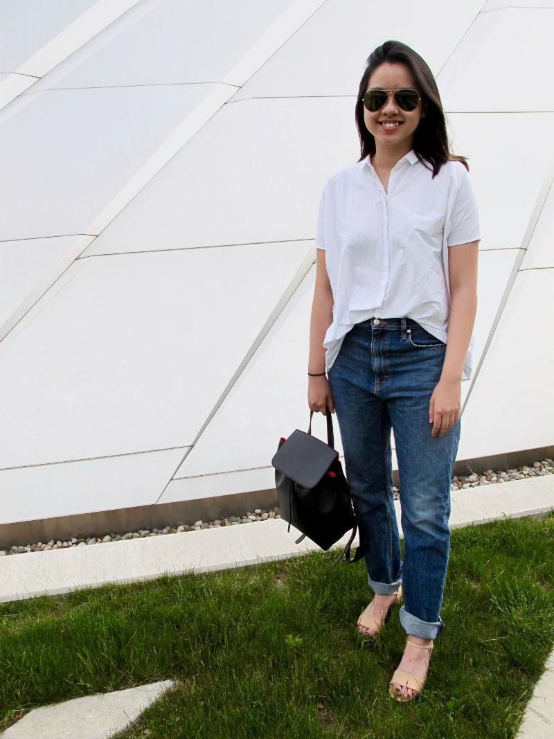 MSU fashion – Student Julia wears boyfriend jeans, a white button down shirt, aviator sunglasses and strappy sandals, plus a minimalist black backpack