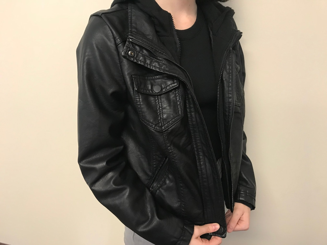 Cara's black motorcycle jacket has an inner knit layer with a hood for added warmth.