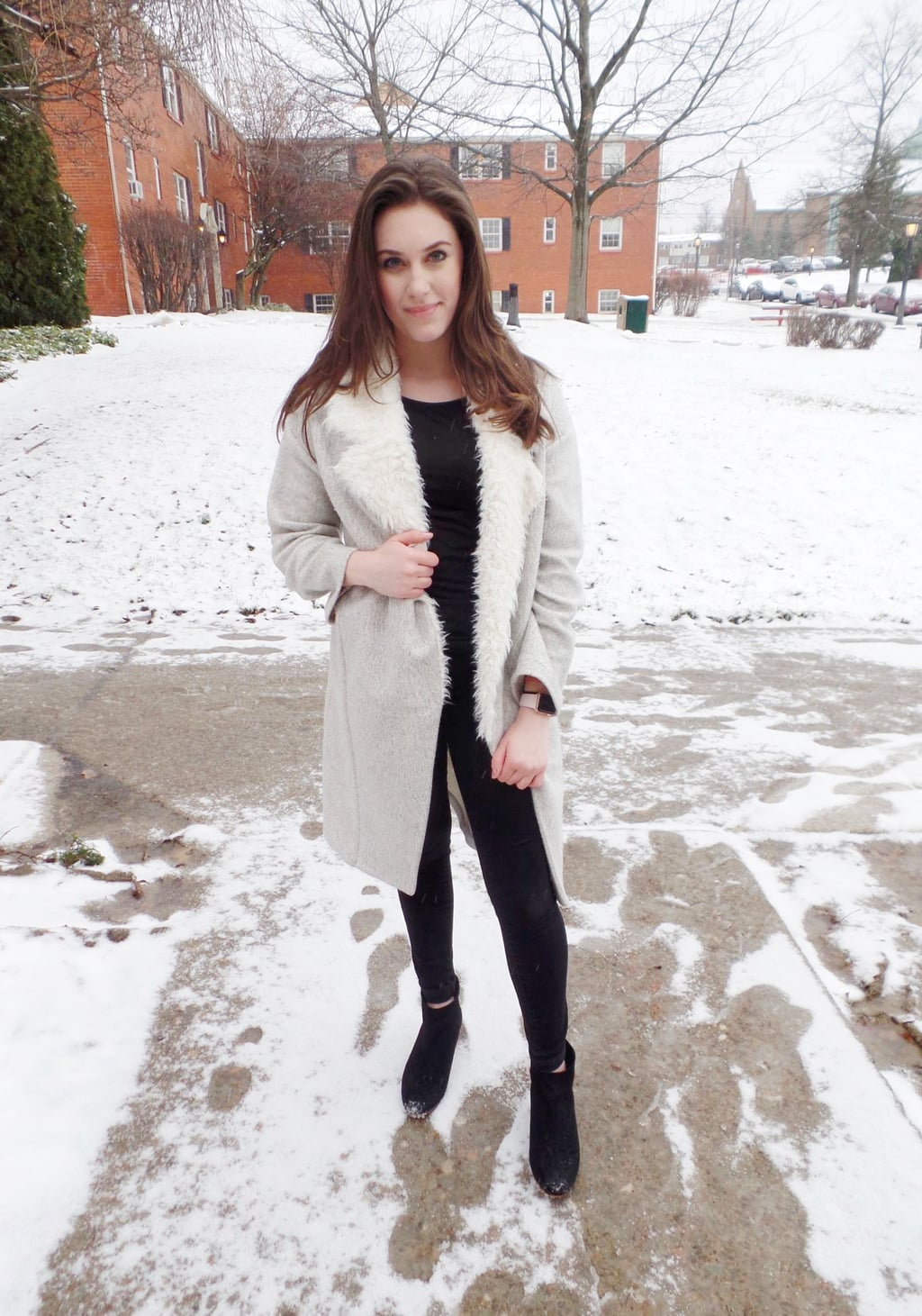 A Mercyhurst University student wears an all black monochromatic outfit made up of a tee, jeans, and booties, with a long grey coat with white fur lapels.
