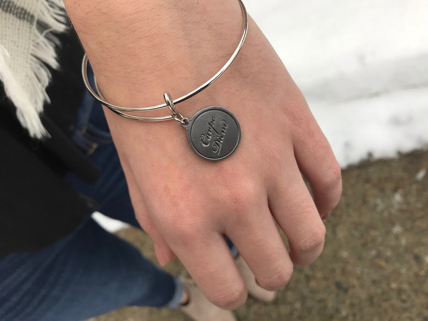Erica wears a silver Alex & Ani bracelet with the inscription