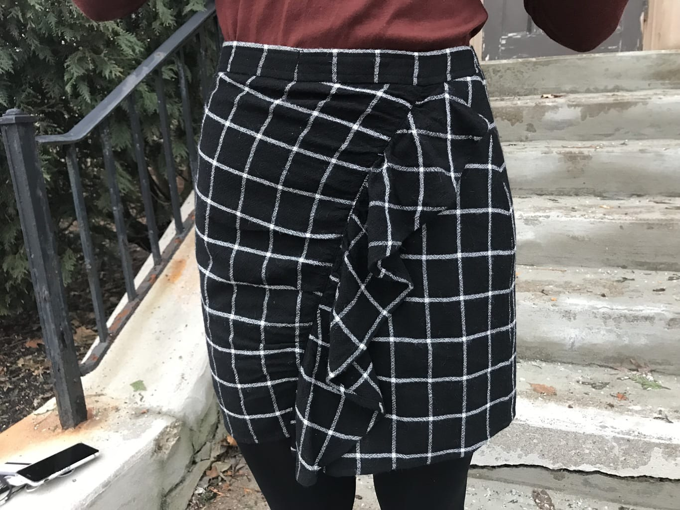 Jillian wears a black fitted skirt with a white windowpane pattern and a front ruffle.