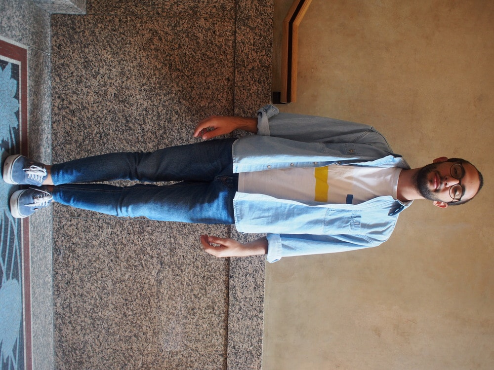Andrea, a student at Politecnico di Milano, wears a white, yellow, blue, and blush graphic tee with a chambray denim shirt over. He pairs it with skinny blue jeans and scuffed up blue vans with white laces.