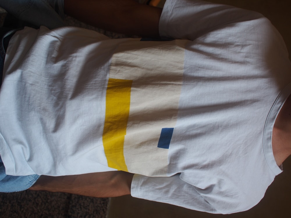 Andrea's simple crew neck white tee has a graphic bright yellow, muted yellow, and blue pattern on the front.