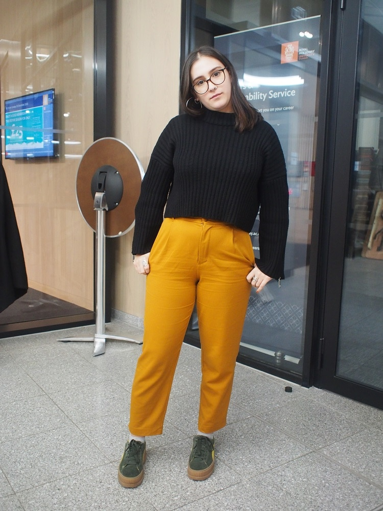 Royal Holloway student Dina wears a chunky black ribbed crop sweater with zippers on the sleeves, high-waisted mustard trousers, and chunky hunter green sneakers.