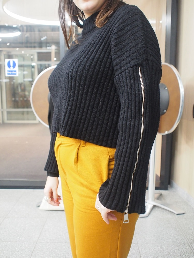 Dina's chunky ribbed crop sweater has silver zippers down the sleeves.