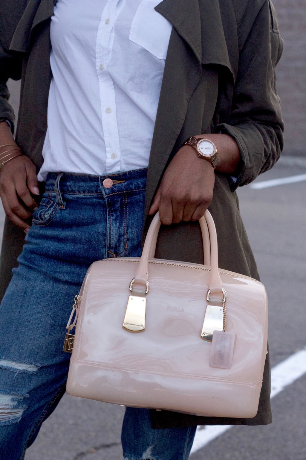 Ultra patent mini blush pink tote bag with gold details, worn with a copper watch.