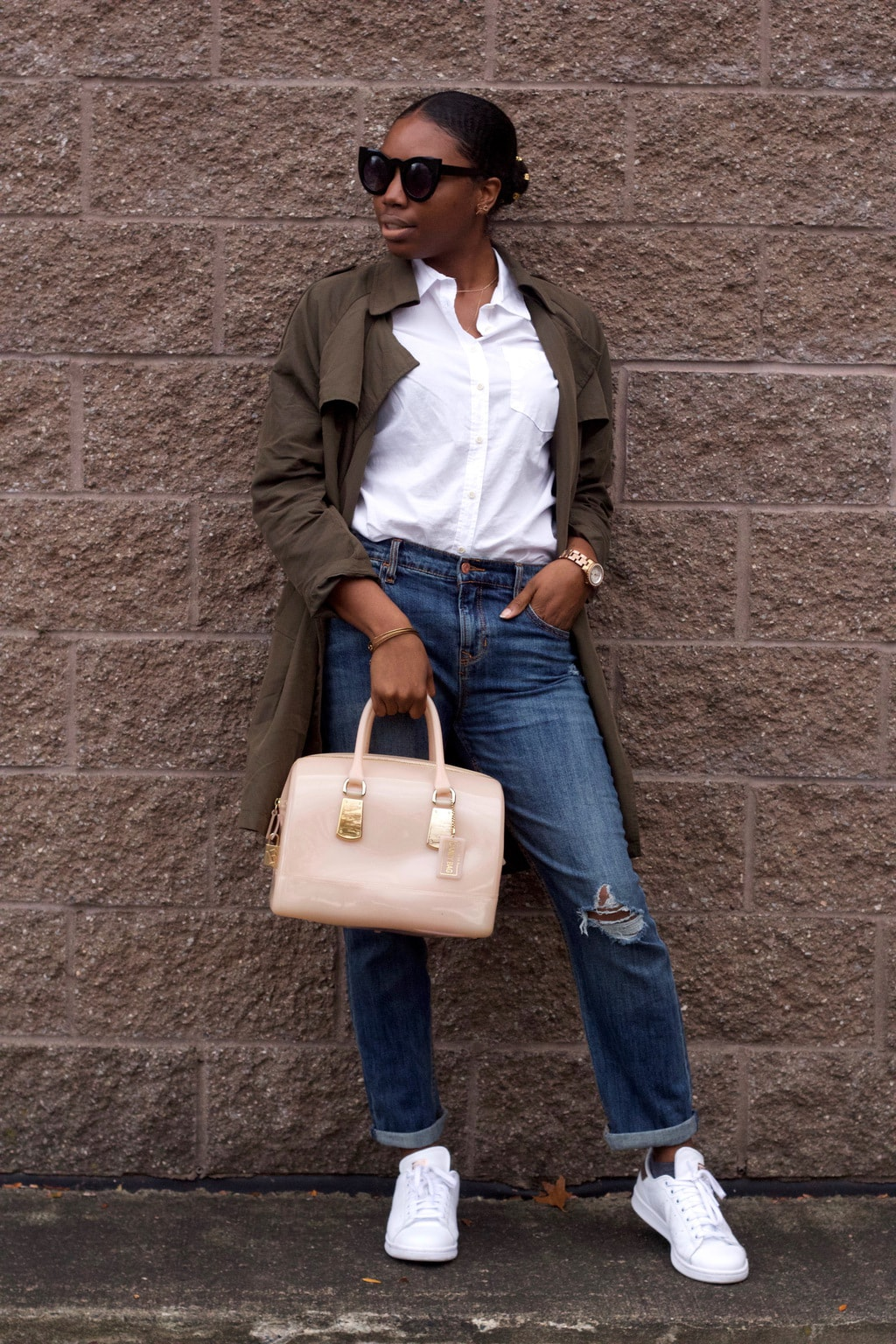 Amani wears a white button-up blouse tucked into loose-fit medium-wash distressed boyfriend jeans with an olive green duster rain jacket and white sneakers. She accessorizes with a blush pink rubberized tote bag and bold cat-eye sunglasses.
