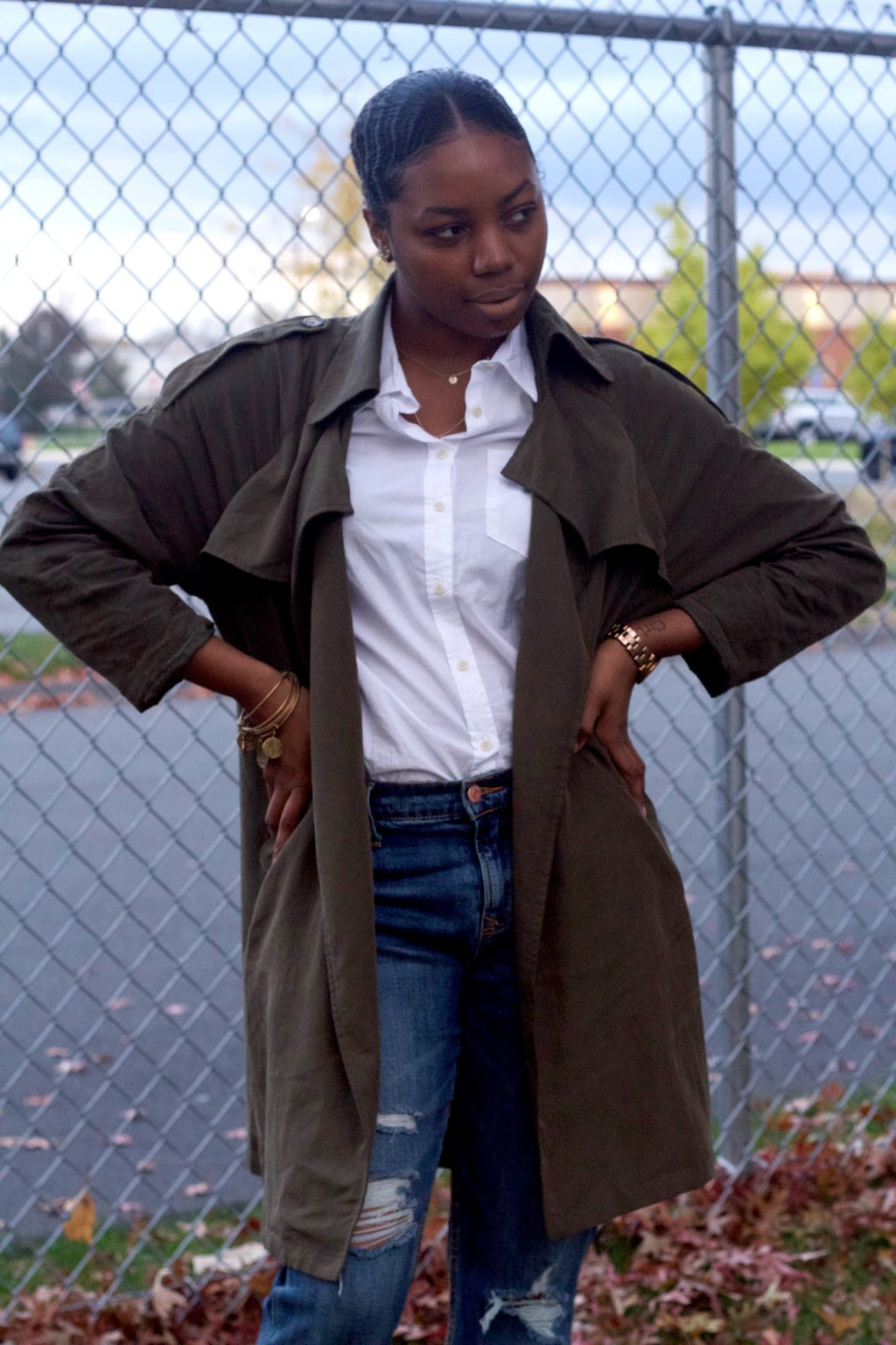 This olive green trench coat outfit is so classy! A green trench is worn with a button-up white blouse tucked in for a classic look.