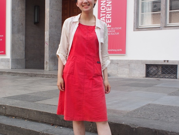 Victoria wears a boxy red vintage dress from Hong Kong with a sheer tan utility shirt on top.