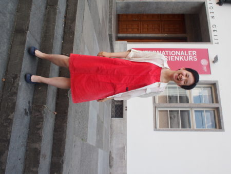 Victoria, a student at Science Po, wears a red utilitarian dress with navy ballet flats and a tan button-up on top.