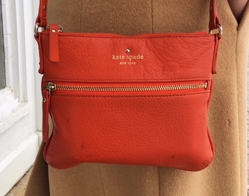 This bright orange Kate Spade crossbody mini purse jhas gold accents and zippers.