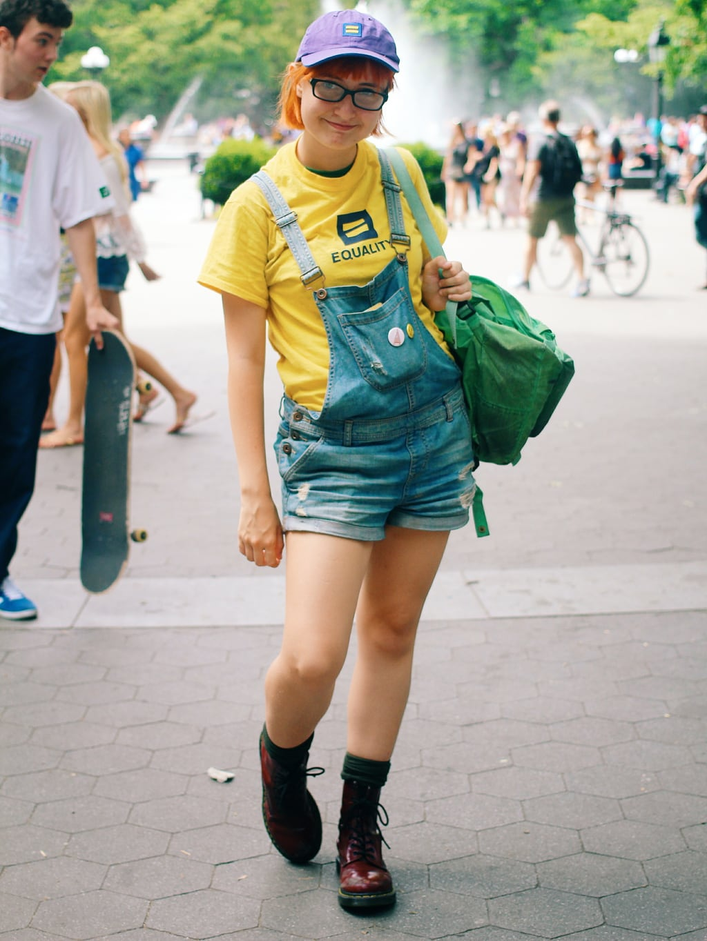 Fashion at School of Visual Arts, NYC - student Kaylee wears a quirky summer outfit idea with an Equality hat and tee shirt, distressed overalls, a green backpack, and maroon Doc Martens boots