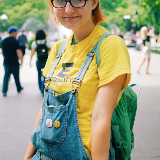 Fashion at School of Visual Arts, NYC - student Kaylee rocks bright red hair, a yellow Equality tee shirt, a green backpack, and overall shorts