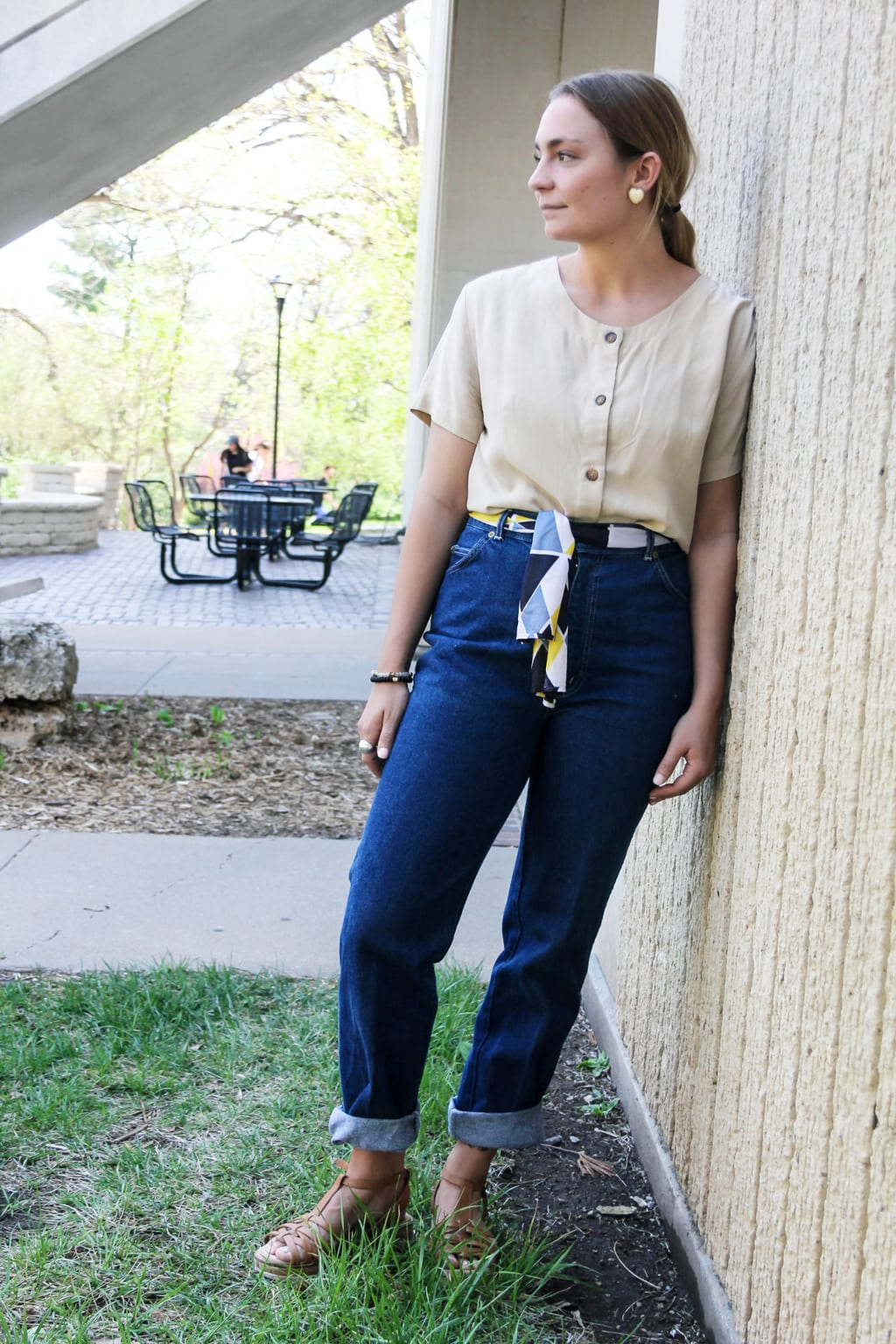 Emilee, a student at Kansas State University, wears a pale yellow scoop neck button-up short sleeve top with brown buttons, high-waisted deep blue denim jeans, a yellow, blue, and black vintage scarf tied as a belt, brown woven sneakers, and heart-shaped earrings.