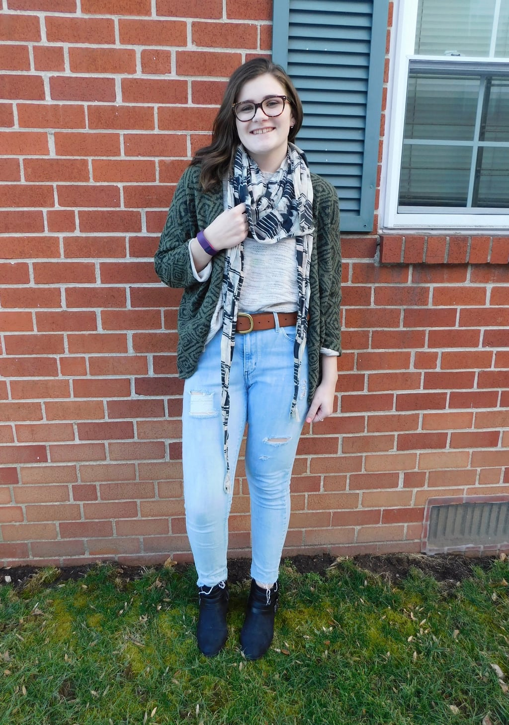Lauren sports a cream sweater top with an olive green geometric print cardigan and a brown belt on her distressed denim skinny jeans. She tops off her look with a bold black and white scarf and black booties.