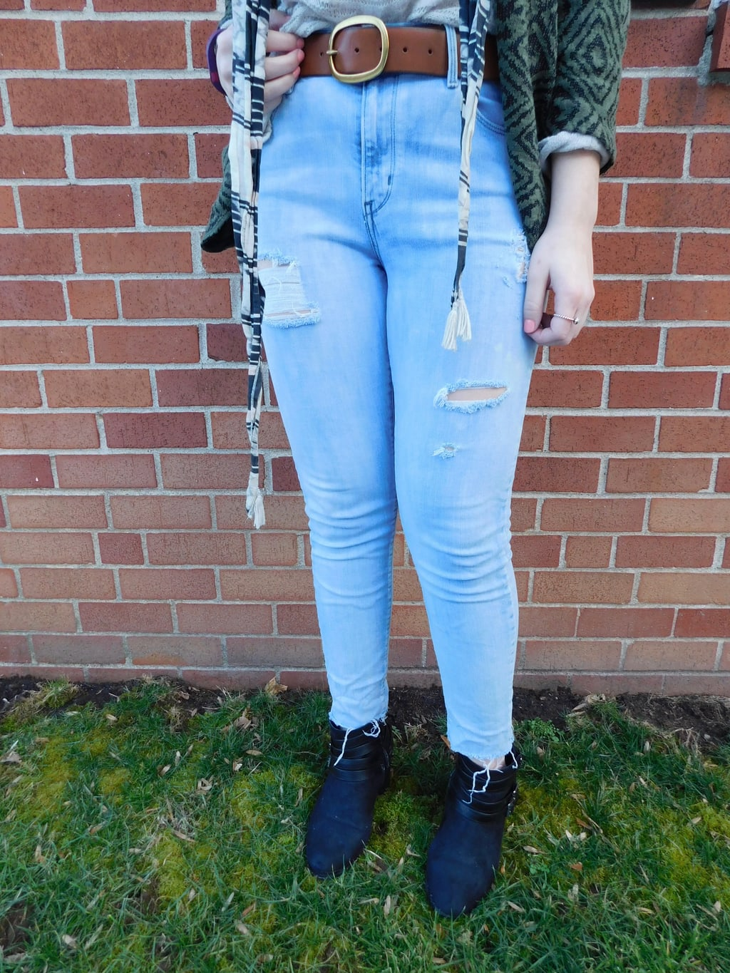 Lauren's light-wash, high waisted distressed denim jeans are held up by a thick brown belt with a gold buckle.