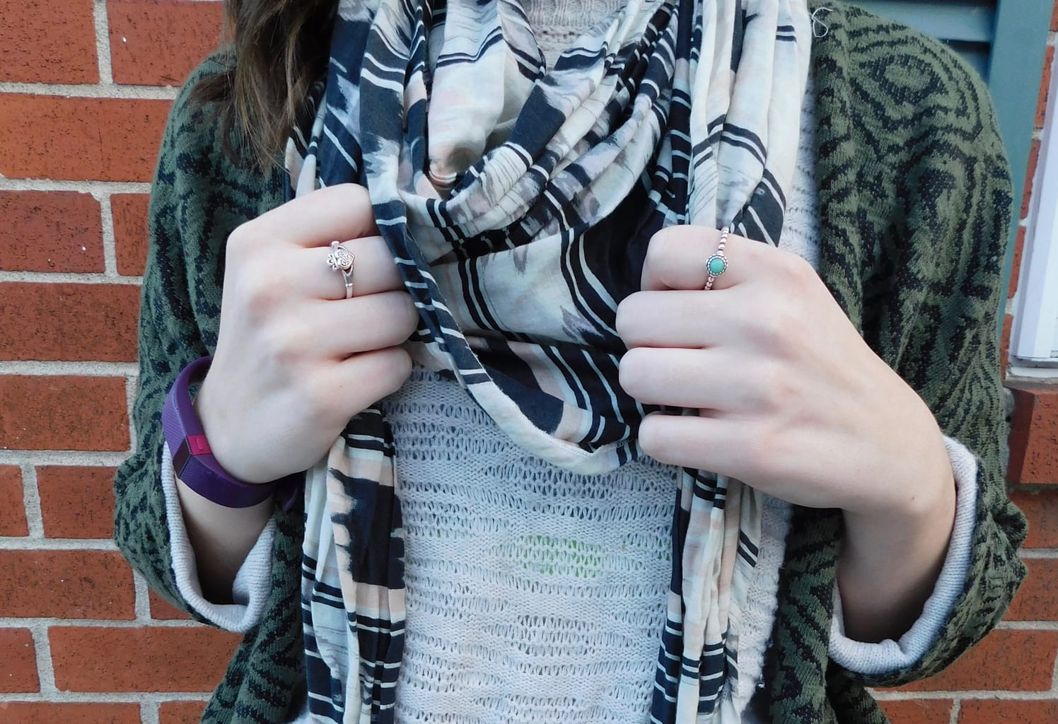 Lauren wears tiny, delicate silver rings, one with a turquoise stone, to compliment her casual look.