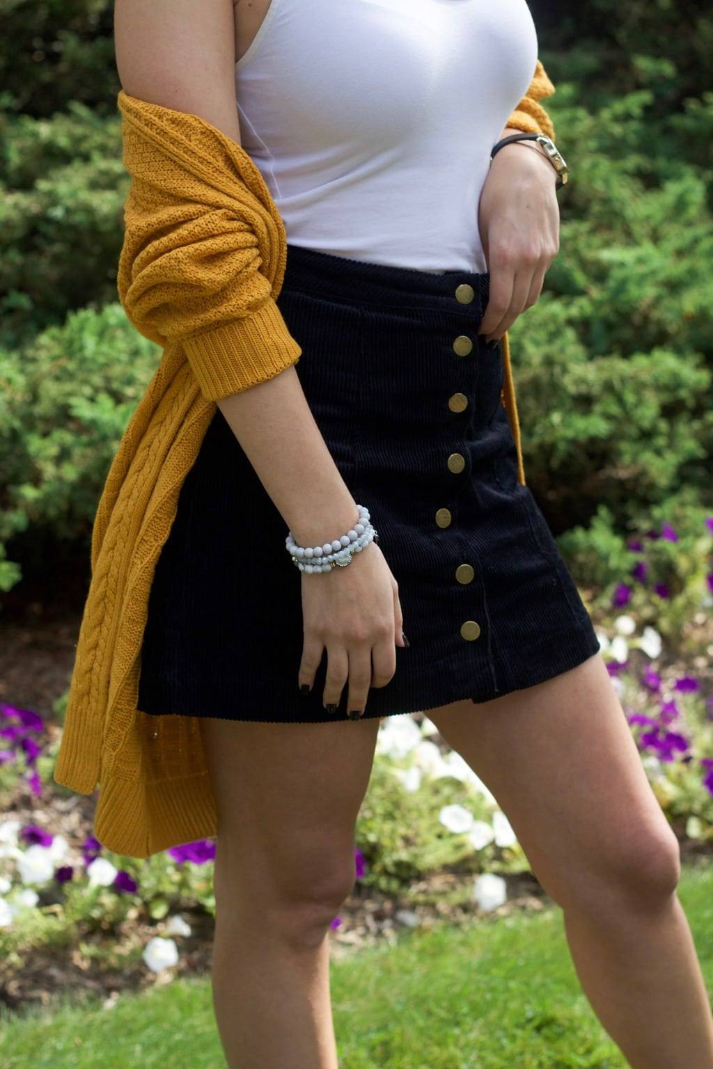 University of Bridgeport student wearing a chunky, slouchy mustard knit cardigan with a navy button-front high-waisted miniskirt and a white camisole tucked in.