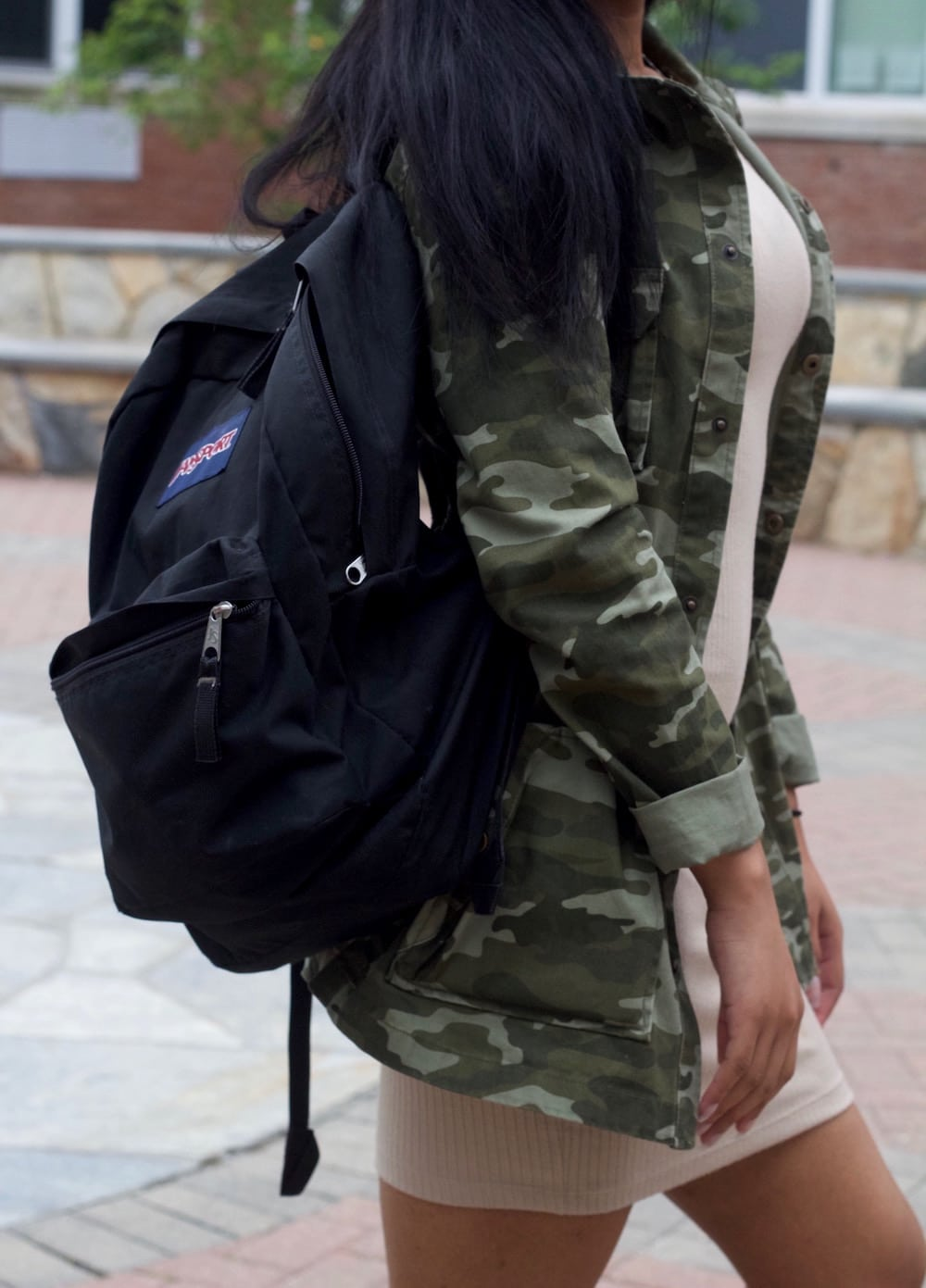 Mix and match: student totes around a black carryall Jansport backpack with her camouflage rain jacket and beige mini dress.