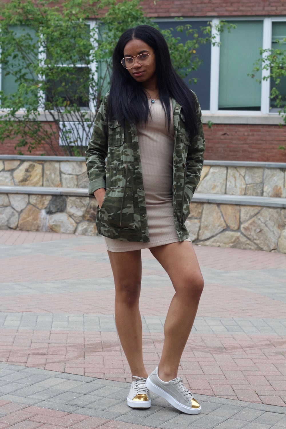 University of Bridgeport student wears a bodycon beige minidress with a camouflage military-inspired rain jacket and grey copper-toed sneakers. She accents her look with oversized glasses for hipster appeal.