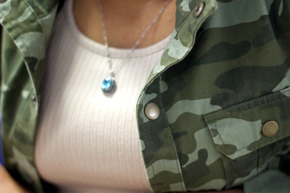 Detail of camouflage jacket over a nude dress with a simple aqua necklace on a silver chain.