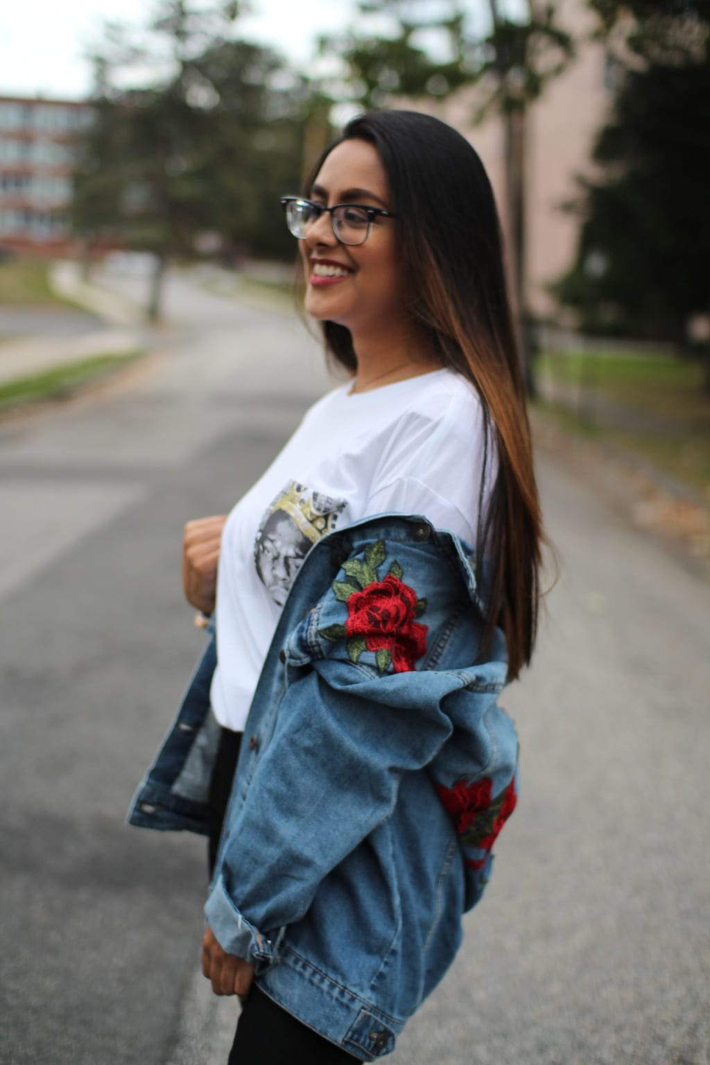 This oversized, distressed denim jacket is embroidered with red roses with green leaves. She wears it with a simple white tee.