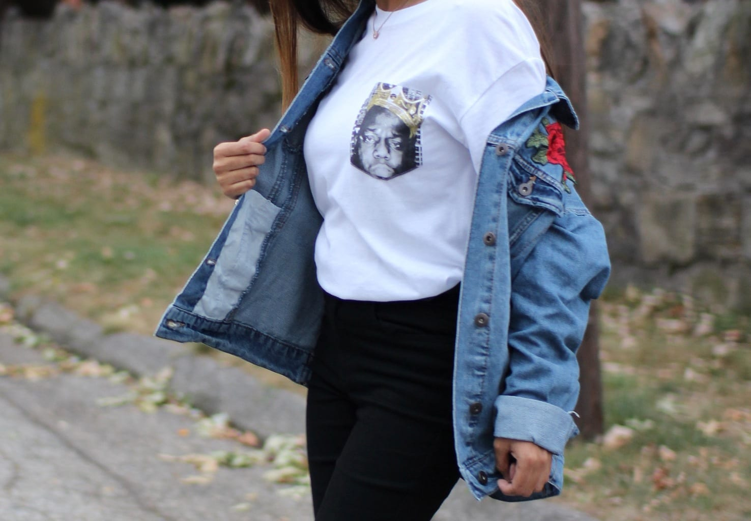 Tasfia's oversized plain white tee has a portrait graphic where a pocket would be. She wears it with a distressed light denim embroidered jacket.