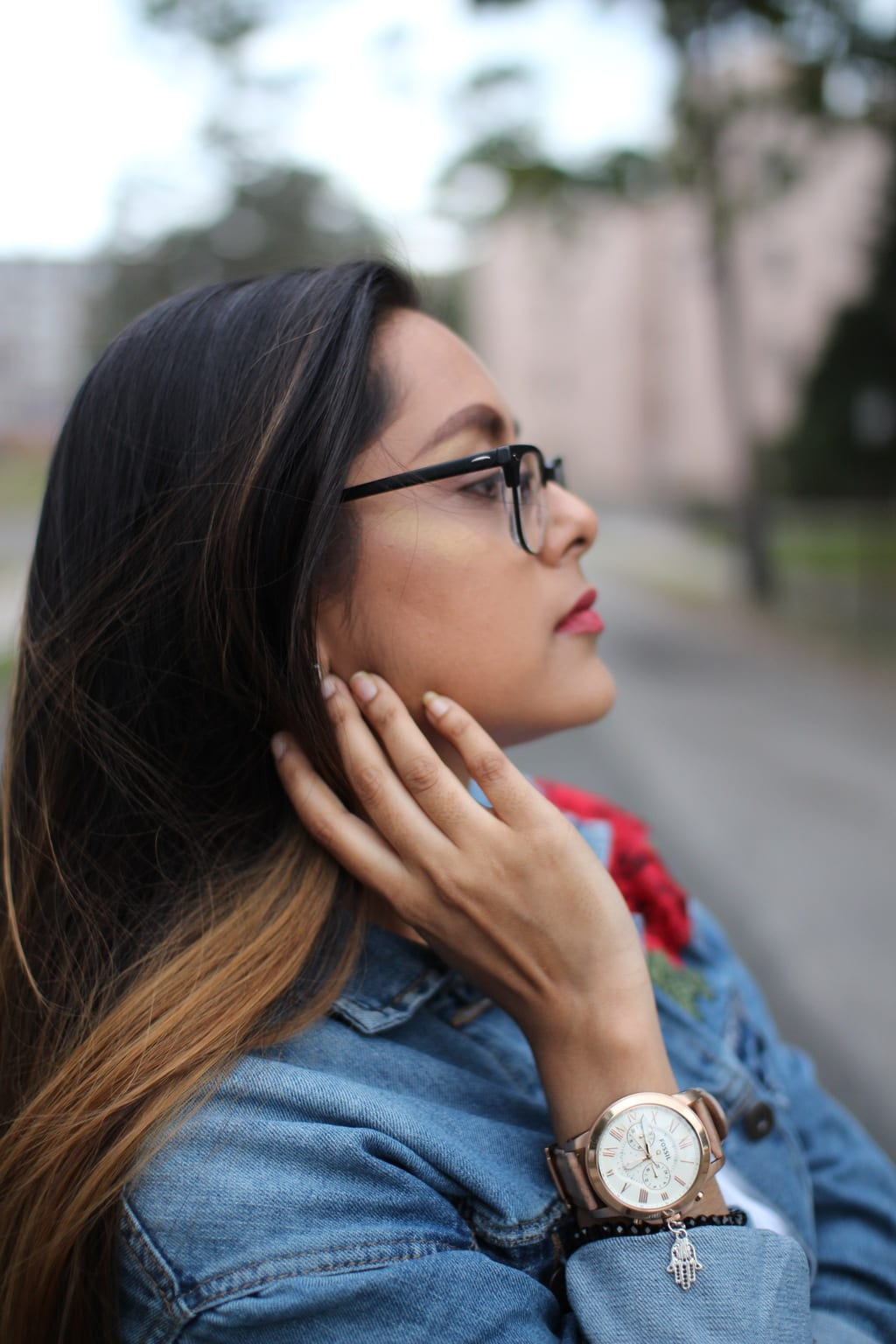 A University of Bridgeport student wears a large whitefaced, rosegold watch with a black beaded bracelet and an oversized denim embroidered jacket.