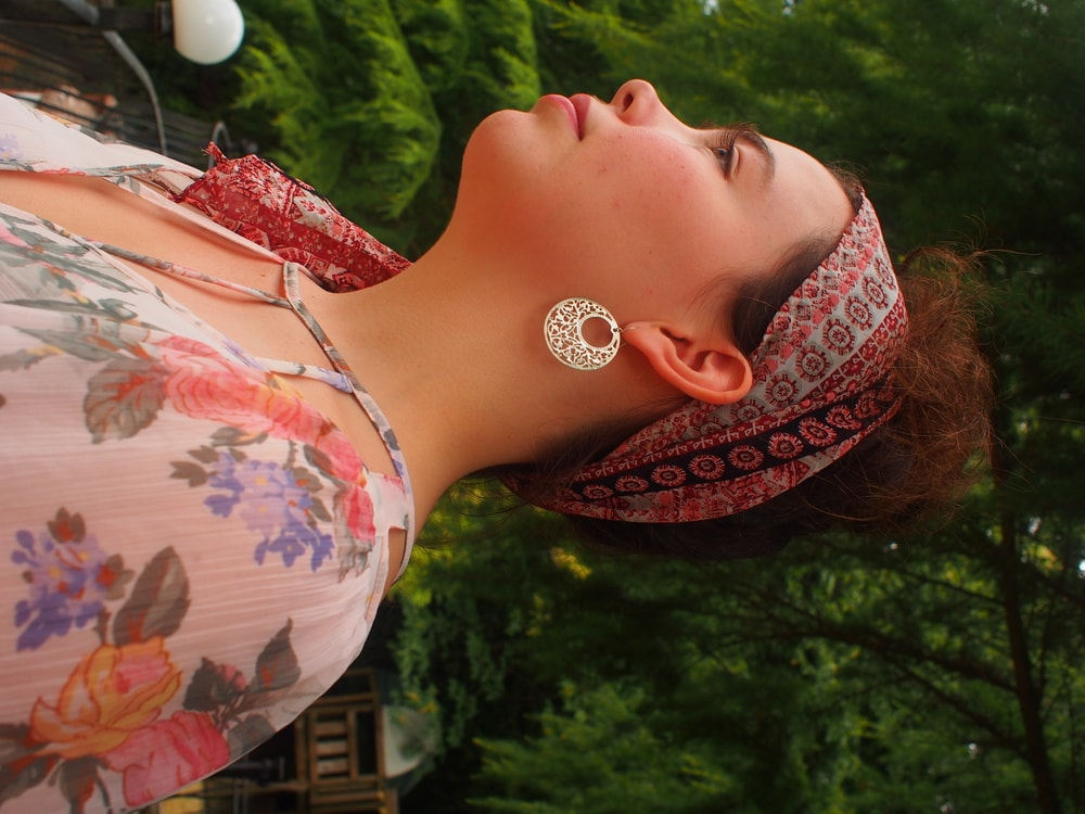 Amy sports a light blue, pink, and black paisley print bandana tied around her head and silver hoop earrings with cutout details.