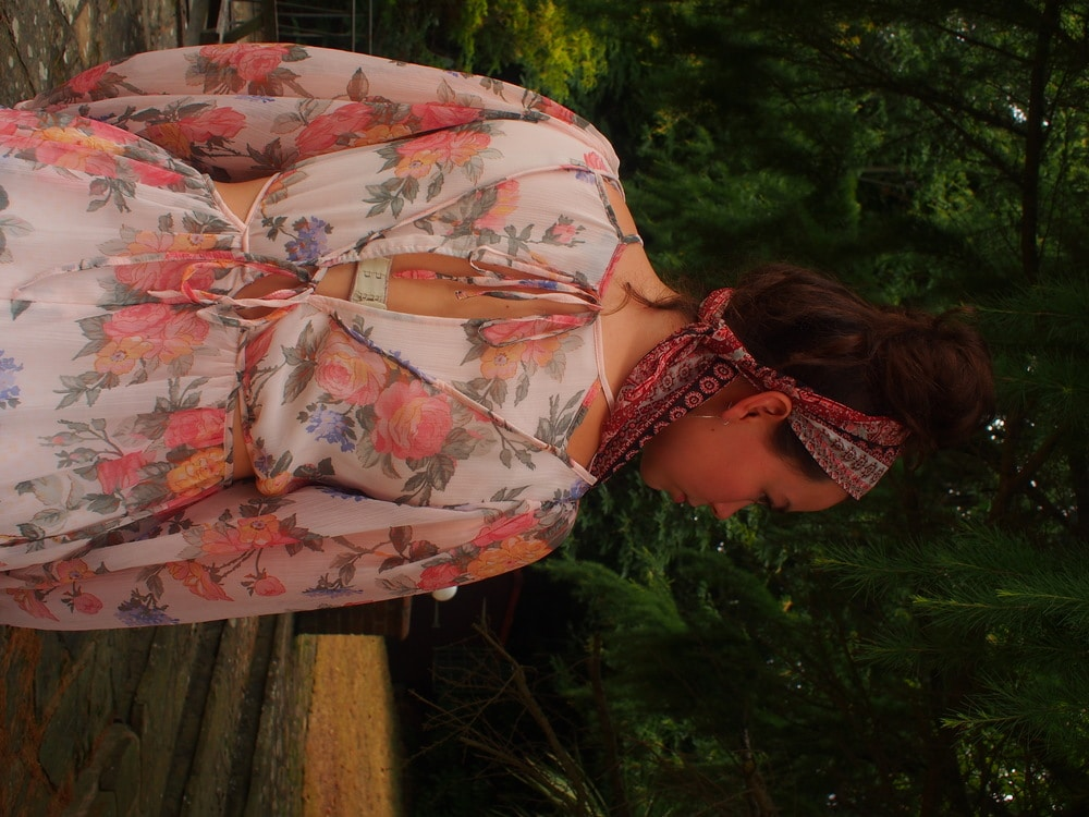 Amy's whimsical floral print chiffon long sleeve maxi dress is cream, green, pink, and orange and has cutout details and ties.