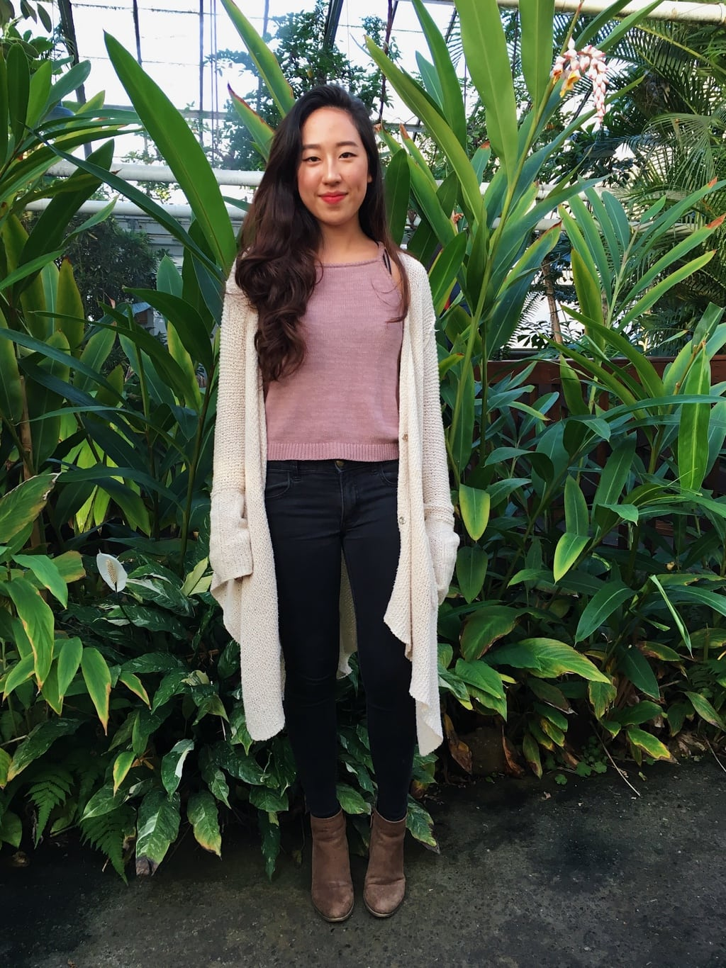 University of Massachusetts Amherst student Aren sports a mauve knit sleeveless top, a long flowy oatmeal knit sweater, dark wash skinny jeans, and chunky brown booties in the campus greenhouse.