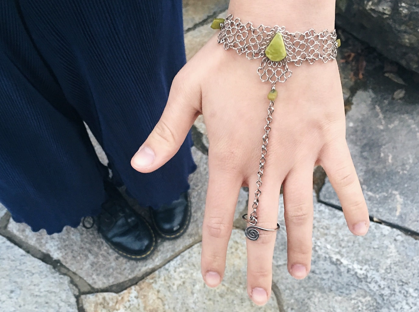 Caeli wears unique silver hand bracelet with detailed metal links that connect a ring to a bracelet. This piece has yellow-green stones to accent.