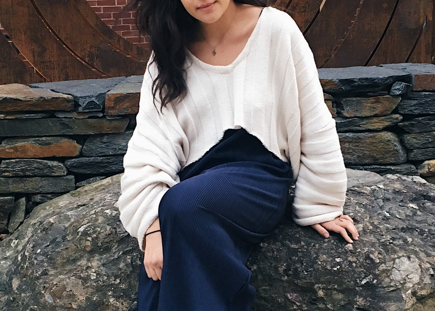 Caeli wears a loose-fitting white striped cropped sweater over a navy blue flowy jumpsuit.