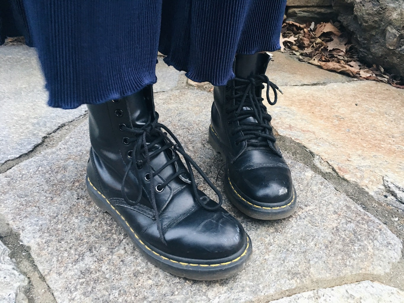 Caeli shows off her rugged black Doc Martens with rubber soles and black laces.