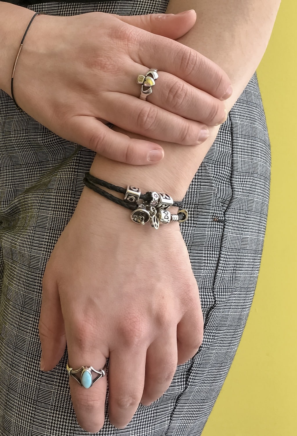 Caroline's simple silver jewelry all flows together. She wears a silver ring with a heart on it, black braided bracelets with silver charms, and a turquoise ring.