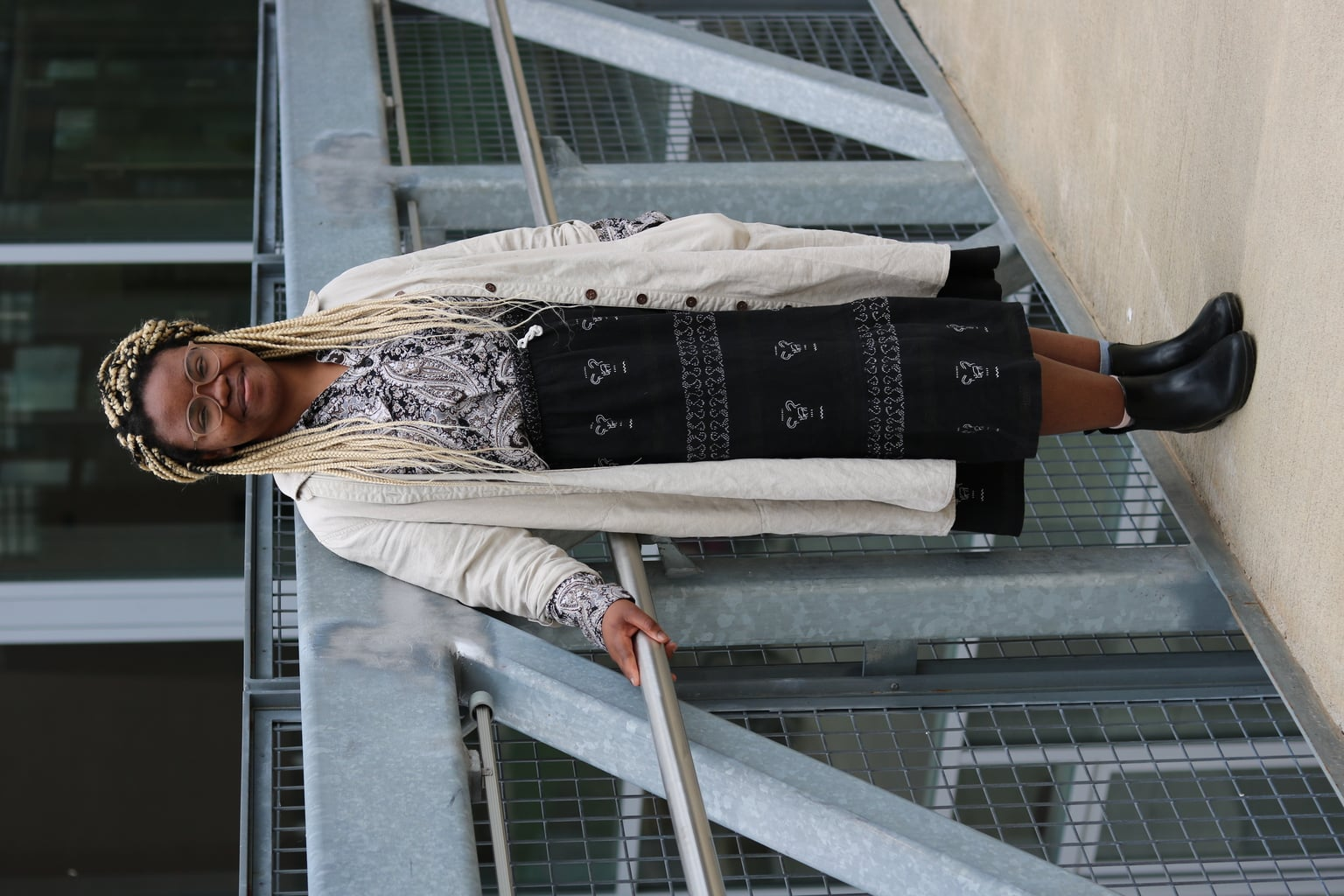 UMass Amherst student Cynthia wears a white and black long sleeve paisley button-up collared shirt tucked into a flowy bohemian midiskirt with delicate white stitching. She pairs it with a long canvas tan trench coat and flat rain boots.