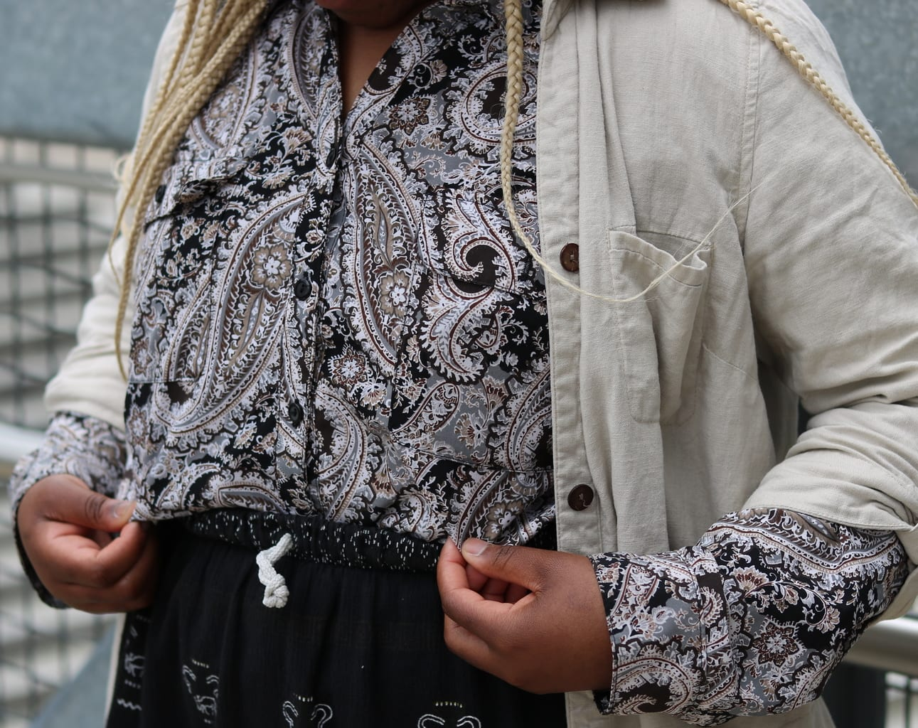 Cynthia's black and white paisley button-up collared shirt has a touch of tan detailing. She tucks it into her midi skirt and wears it with a light linen trench coat.