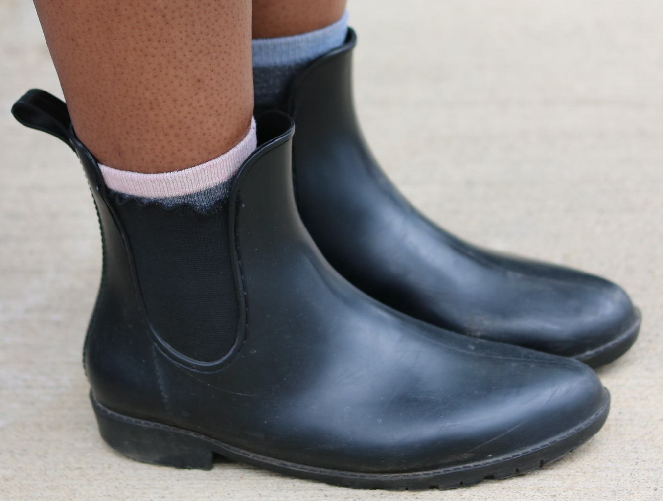 Cynthia wears flat black Chelsea rubber rain boots with different colored socks peeking out.