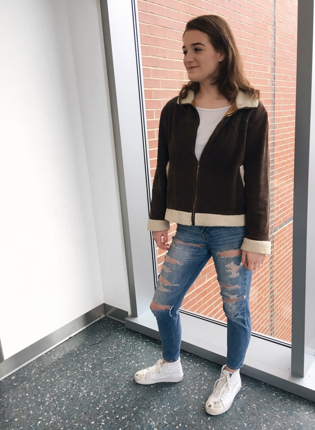 University of Massachusetts student Erin wears a brown corduroy jacket with shearling details, a white tee, ultra distressed denim jeans, and white Vans.